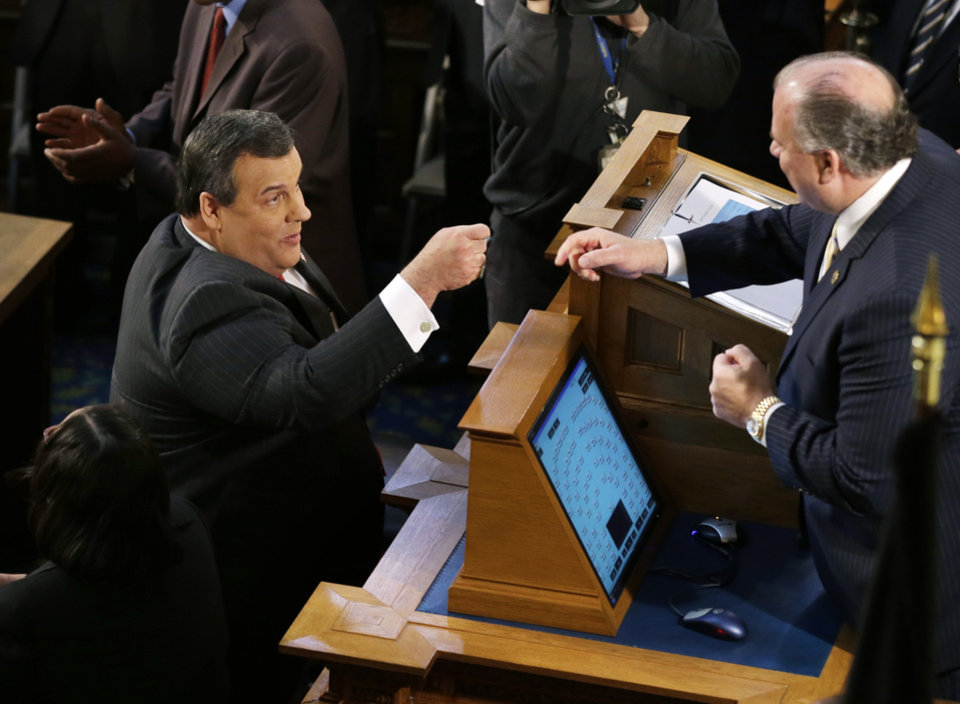 Photo - Republican New Jersey Gov. Chris Christie reaches up to fist bump with Senate President Stephen M. Sweeney, right, D-Thorofare, N.J., as Christie prepares to deliver his State Of The State address at the Statehouse, Tuesday, Jan. 8, 2013, in Trenton, N.J.  (AP Photo/Mel Evans)