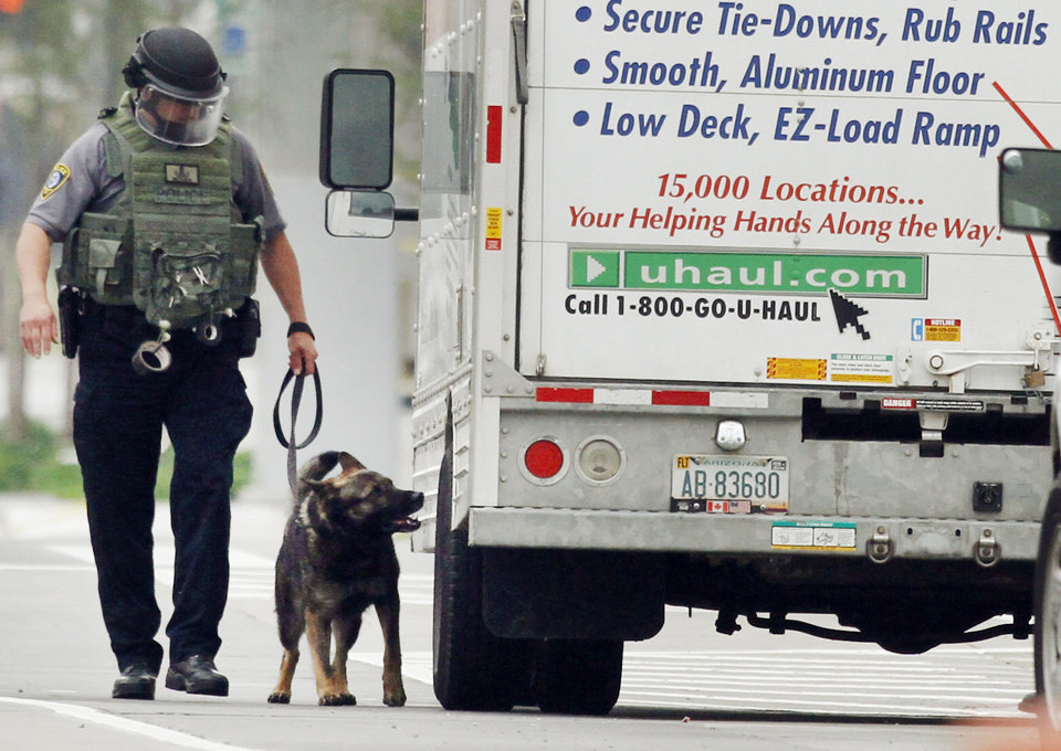 Photo - BOMB SCARE: An Oklahoma City K-9 officer checks for explosives as they search a U-Haul truck parked on Walker Avenue in downtown Oklahoma City , Wednesday April 17, 2013. Photo By Steve Gooch, The Oklahoman ORG XMIT: OKC1303121532440650