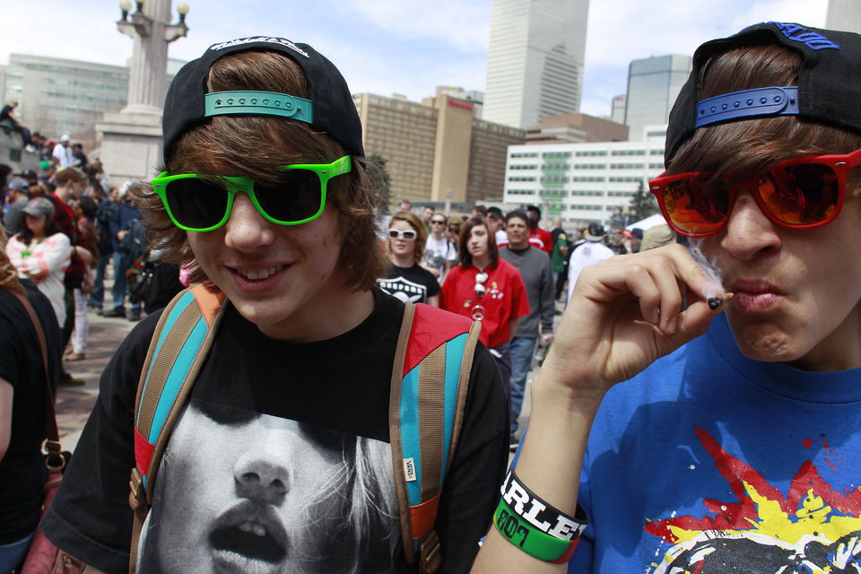 Photo - Youths smoke marijuana at the Denver 4/20 pro-marijuana rally at Civic Center Park in Denver, Saturday, April 20, 2013. Even before the passage in November 2012 of Colorado Amendment 64 that promised the legalization of marijuana for recreational use, April 20th has for years been a celebration of marijuana counterculture, and the 2013 rally was expected to draw larger crowds than previous years. (AP Photo/Brennan Linsley)
