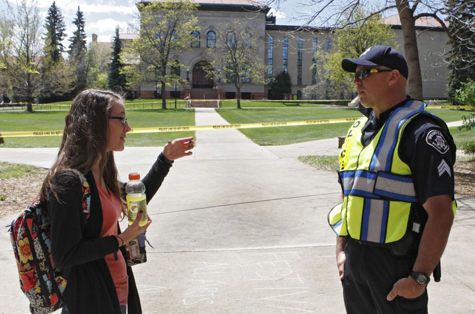 Photo -   Boulder County Sheriff Sgt. Jeff Goetz, gives directions to sophomore Baylee Thenell at the Norlin Quad at the University of Colorado in Boulder, Colo., on Friday, April 20, 2012. The university closed the area and the campus from visitors to prohibit an annual 420 marijuana smoke out. (AP Photo/Ed Andrieski)