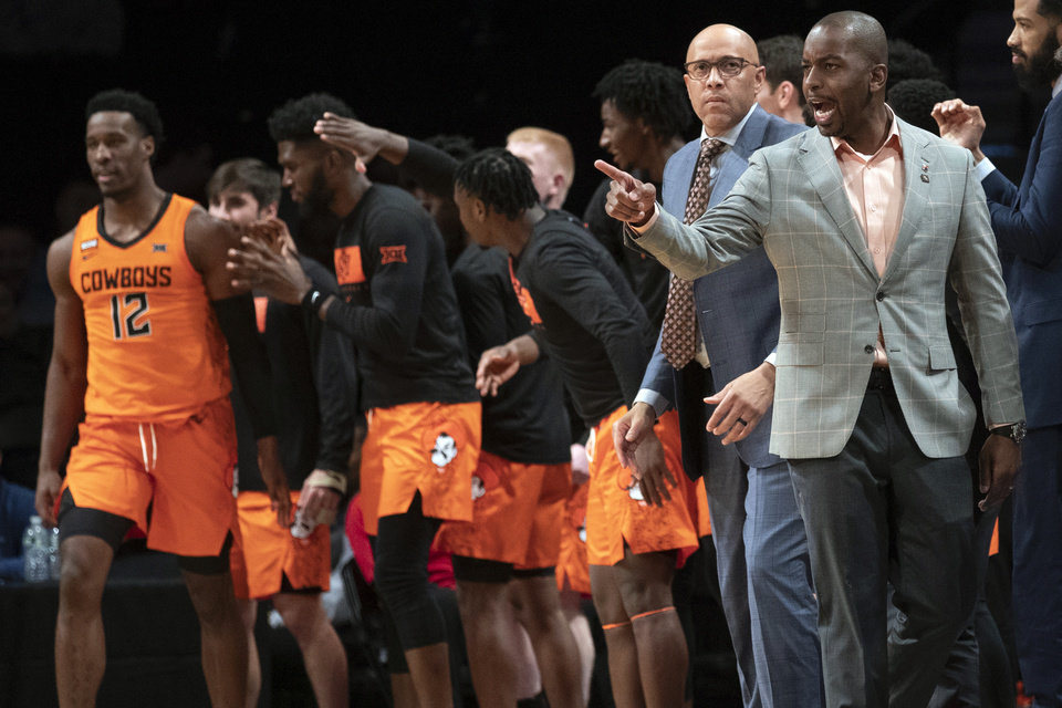 Photo - Oklahoma State head coach Mike Boynton, right, reacts during the second half of an NCAA college basketball game against Mississippi in the final of the NIT Season Tip-Off tournament, Friday, Nov. 29, 2019, in New York. Oklahoma State won 78-37. (AP Photo/Mary Altaffer)