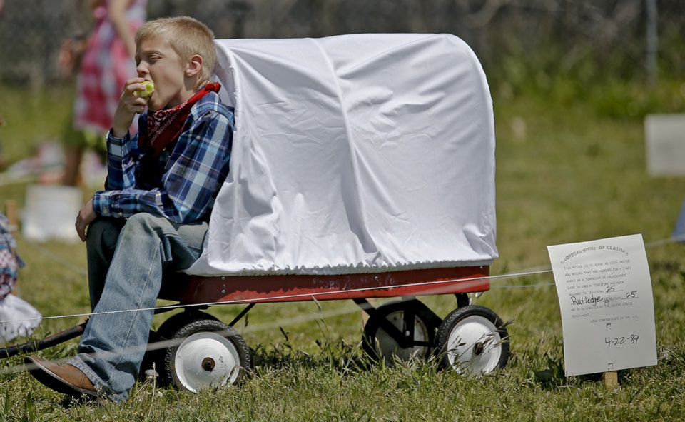Photo - Weston Rutledge sits in his wagon while eating an apple during the Oklahoma Land Run celebration at Mustang Trails Elementary on Monday, April 22, 2013, in Mustang, Okla.   Photo by Chris Landsberger, The Oklahoman