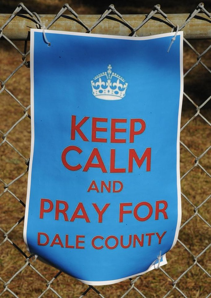 A sign encouraging prayer for a 5-year-old boy being held hostage, hangs on a fence surrounding Midland City Elementary school Wednesday, Feb. 3, 2013, in Midland City, Ala. Authorities say Jim Lee Dykes, 65 — a decorated Vietnam-era veteran known as Jimmy to neighbors — gunned down a school bus driver and then abducted a 5-year-old boy from the bus, taking him to an underground bunker on his rural property. The driver, 66-year-old Charles Albert Poland Jr., who was shot trying to protect children on his bus, was buried Sunday. (AP Photo/AL.com, Joe Songer)