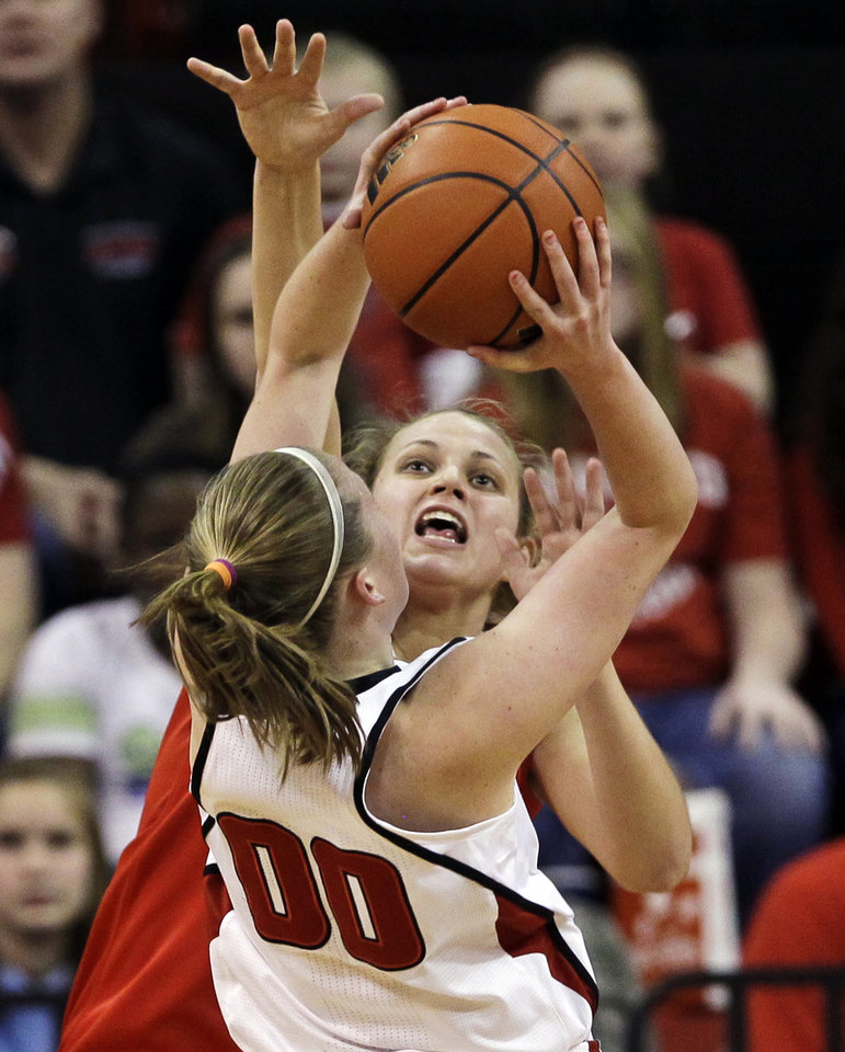 Ohio State's Amy Scullion, rear, defends against a layup by Nebraska's Lindsey Moore (00) in the first half of their NCAA college basketball game in Lincoln, Neb., Sunday, Feb. 26, 2012. (AP Photo/Nati Harnik)