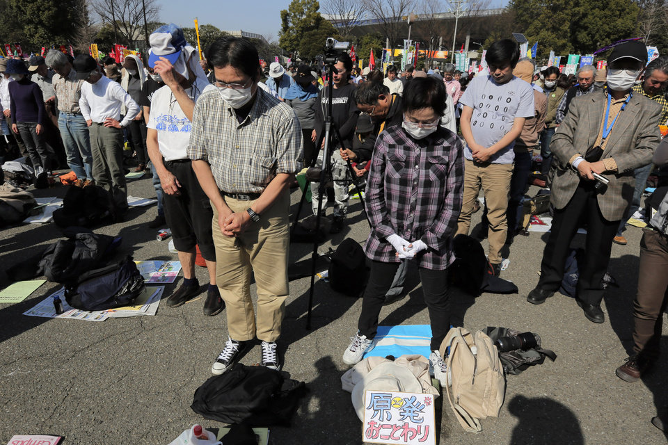 Photo - Protesters observe a moment of silence for the victims of the March 11, 2011 earthquake and tsunami during a rally against nuclear power plants at a park  in Tokyo, Saturday, March 9, 2013. Thousands of people rallied in a Tokyo park Saturday, demanding an end to atomic power, and vowing never to give up the fight, despite two years of little change after the nuclear disaster in Fukushima, northeastern Japan. (AP Photo/Itsuo Inouye)