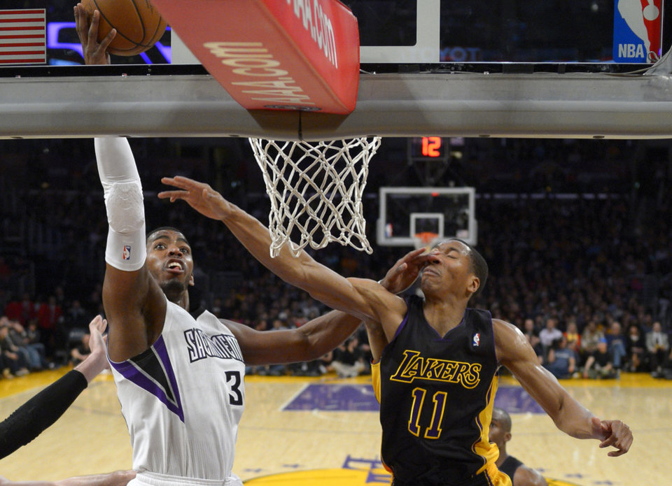 Photo - Sacramento Kings forward Jason Thompson, left, shoots as Los Angeles Lakers forward Wesley Johnson is hit in the face during the first half of an NBA basketball game on Friday, Feb. 28, 2014, in Los Angeles. (AP Photo/Mark J. Terrill)