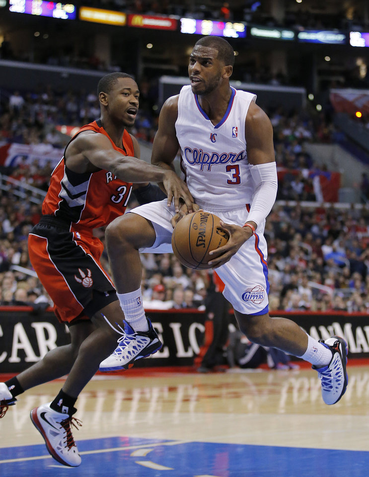 Los Angeles Clippers' Chris Paul, right, is defended by Toronto Raptors' Terrence Ross in the first half of an NBA basketball game in Los Angeles, Sunday, Dec. 9, 2012. (AP Photo/Jae C. Hong)