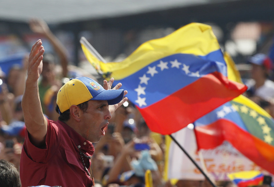 Opposition presidential candidate Henrique Capriles cheers with supporters during a campaign rally at Bolivar Avenue in Caracas, Venezuela, Sunday, April 7, 2013. Capriles is running against ruling party candidate Nicolas Maduro in next weekend\'s presidential election.(AP Photo/Ariana Cubillos)