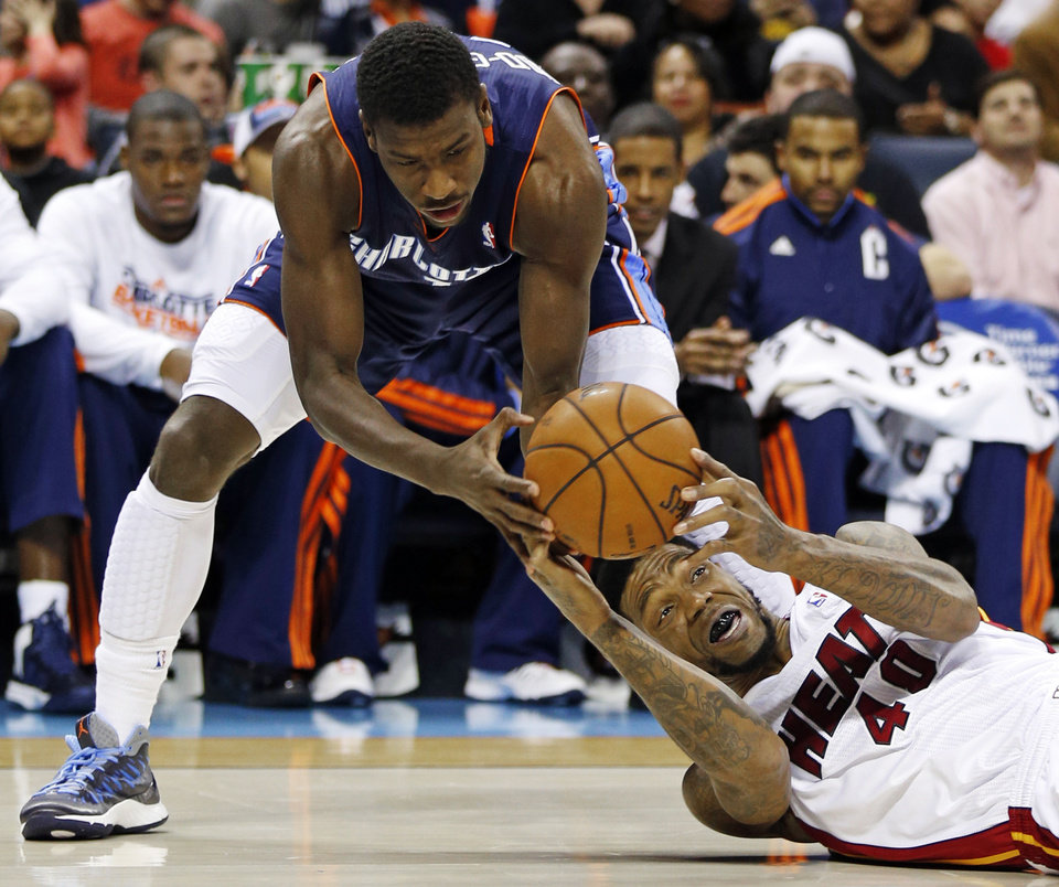 Miami Heat's Udonis Haslem, bottom, looks to pass as Charlotte Bobcats' Michael Kidd-Gilchrist, top, defends during the first half of an NBA basketball game in Charlotte, N.C., Wednesday, Dec. 26, 2012. (AP Photo/Chuck Burton)