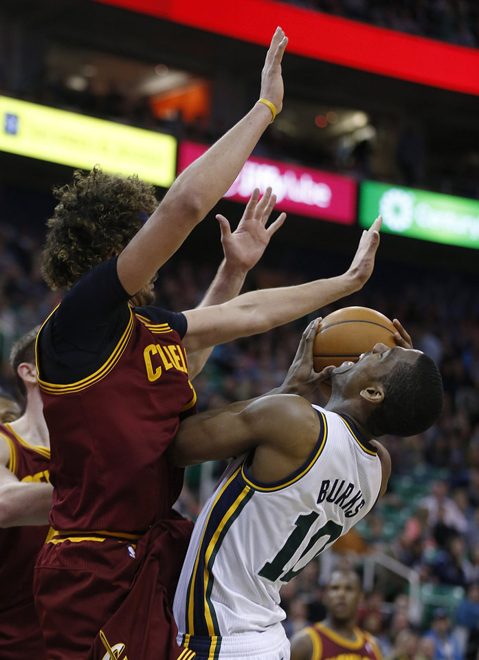 Photo - Utah Jazz's Alec Burks, right, is fouled by Cleveland Cavalier's Anderson Varejao during the second half of an NBA basketball game in Salt Lake City, Friday, Jan. 10, 2014. Cavaliers beat the Jazz 113-102. (AP photo/George Frey)