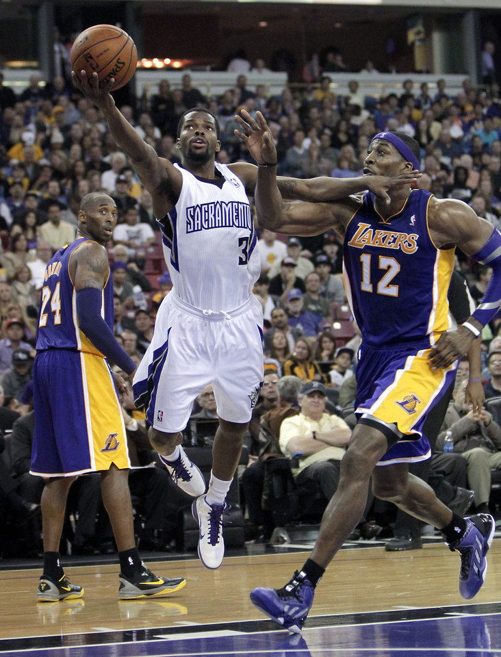 Photo -   Sacramento Kings guard Aaron Brooks, center, drives to the basket against Los Angeles Lakers center Dwight Howard, right, as Kobe Bryant, left, watches during the second half of an NBA basketball game in Sacramento, Calif., Wednesday, Nov. 21, 2012. The Kings won 113-97. (AP Photo/Rich Pedroncelli)