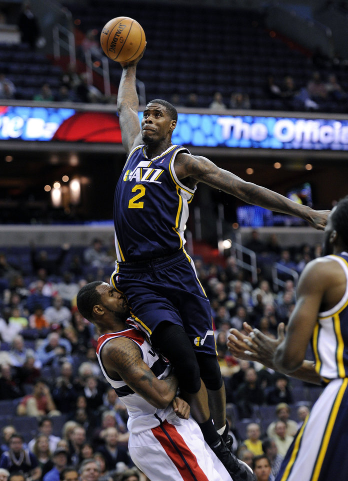 Utah Jazz's Marvin Williams (2) is fouled by Washington Wizards' Trevor Booker, left, during the first half of an NBA basketball game, Saturday, Nov. 17, 2012, in Washington. (AP Photo/Nick Wass)