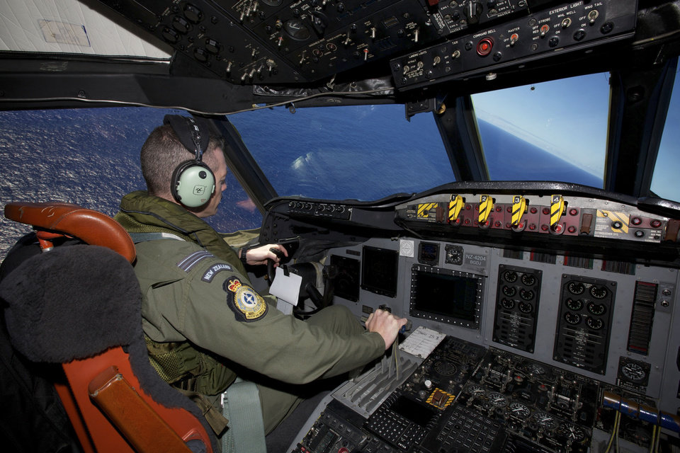 Photo - Captain Flt. Lt. Tim McAlevey of the Royal New Zealand Air Force flies a P-3 Orion in search for the missing Malaysia Airlines Flight 370 over the Indian Ocean, Friday, April 11, 2014. Authorities are confident that signals detected deep in the Indian Ocean are from the missing Malaysian jet's black boxes, Australian Prime Minister Tony Abbott said Friday, raising hopes they are close to solving one of aviation's most perplexing mysteries. Abbott told reporters in Shanghai that crews hunting for Flight 370 have zeroed in on a more targeted area in their search for the source of the sounds, first heard on Saturday. (AP Photo/Richard Wainwright, Pool)