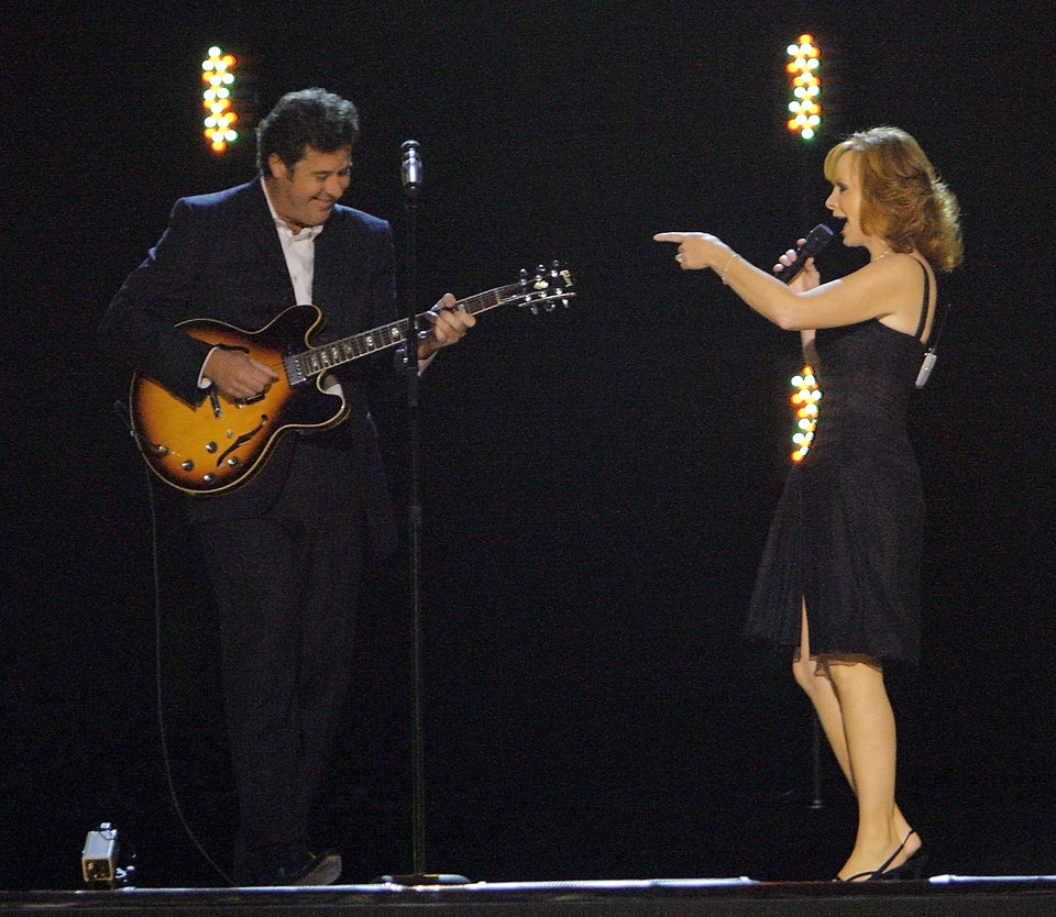 Photo - Vince Gill and Reba McEntire perform during the Centennial Spectacular to celebrate the 100th birthday of the State of Oklahoma at the Ford Center on Friday, Nov. 16, 2007, in Oklahoma City, Okla. Photo By CHRIS LANDSBERGER, The Oklahoman