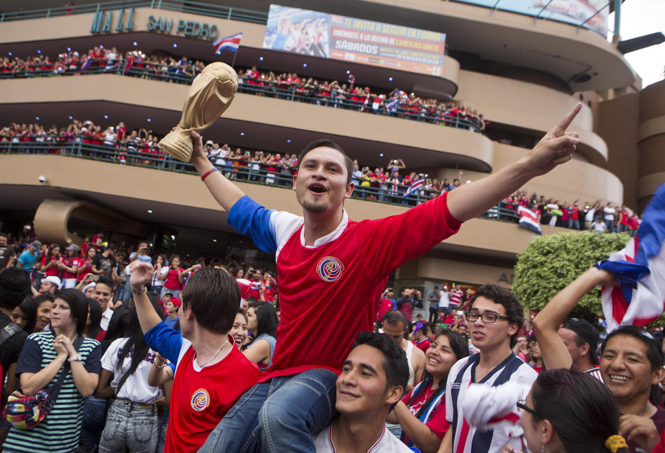 Photo - A Costa Rica soccer fan holds up a replica of the World Cup trophy as people celebrate Costa Rica's victory over Greece at a Brazil World Cup round of 16 game in San Jose, Costa Rica, Sunday, June 29, 2014. Costa Rica won a penalty shootout 5-3 after the match ended 1-1 following extra time. (AP Photo/Esteban Felix)