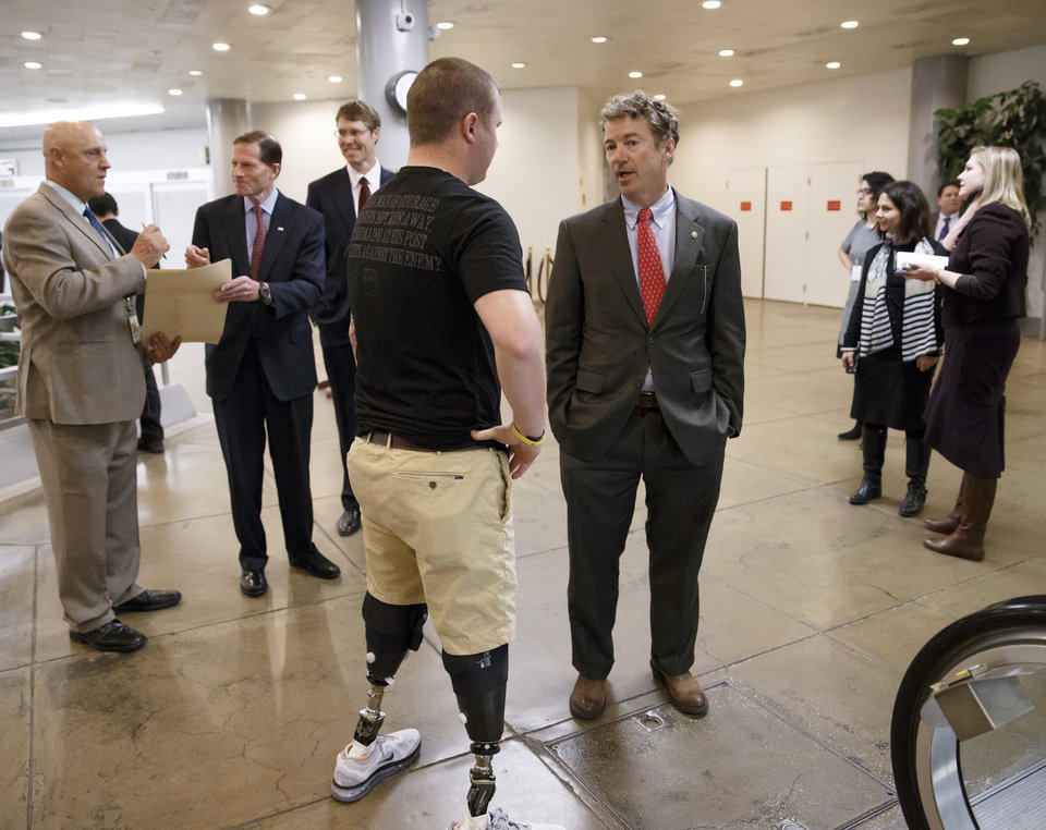 Photo - Sen. Rand Paul, R-Ky., a member of the Senate Foreign Relations Committee, center, stops to speak to a wounded military veteran as he and other lawmakers make their way to the chamber to advance a bill providing $1 billion in loan guarantees to Ukraine as President Barack Obama meets with U.S. allies in Europe to punish Moscow for its annexation of the Crimean peninsula, at the Capitol in Washington, Monday, March 24, 2014.  (AP Photo/J. Scott Applewhite)