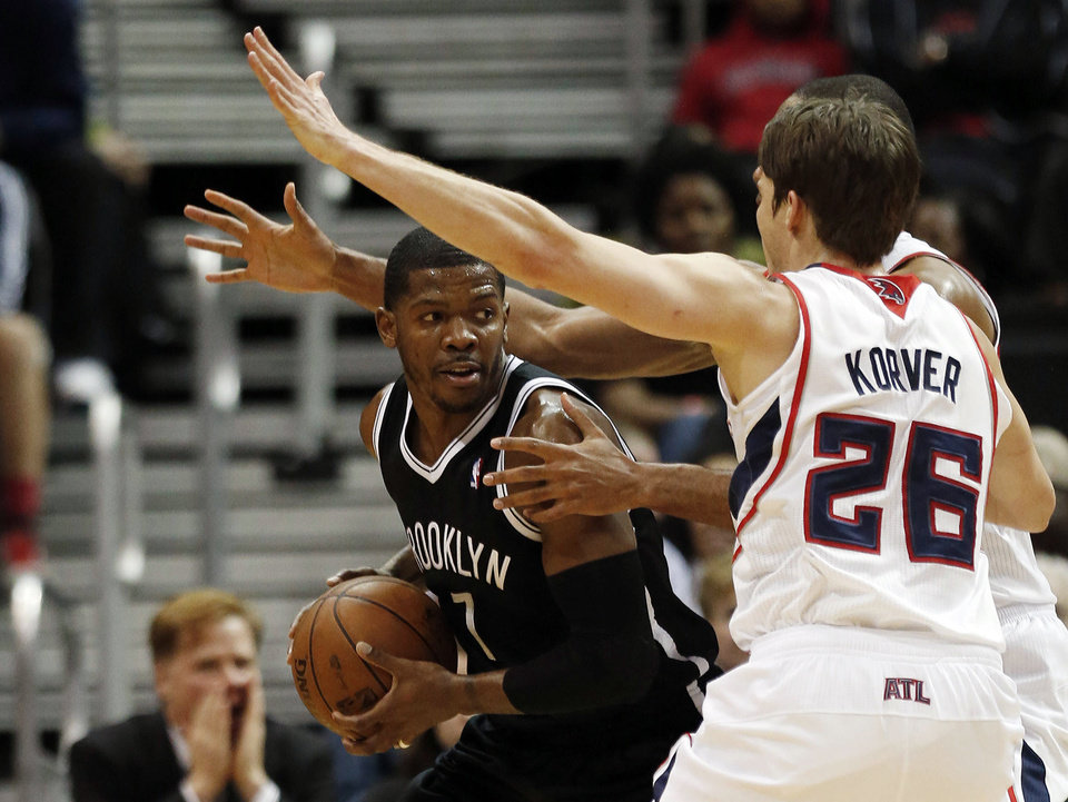 Brooklyn Nets shooting guard Joe Johnson (7) is covered by Atlanta Hawks' Al Horford (obscured) and Kyle Korver (26) in the first half of an NBA basketball game on Wednesday, Jan. 16, 2013, in Atlanta. (AP Photo/John Bazemore)