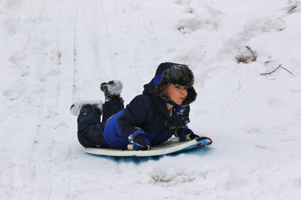 Photo - Owen sleds down a hill while at the park with their grandmother, Jeanne Hapton, at Bickham Rudkin Park in Edmond, Wednesday, February 5, 2020.  [Photo by Doug Hoke/The Oklahoman]