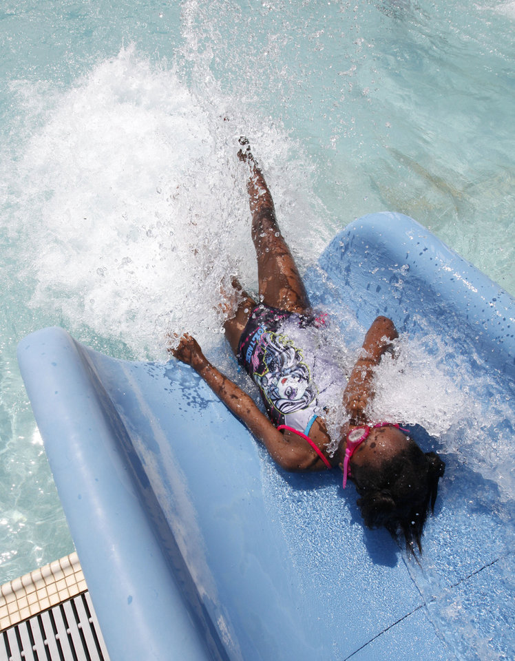Photo -  Makayla Lewis, 8, slides down of one of the water slides at Pelican Bay Aquatic Center in Edmond. Photo by Paul Hellstern, The Oklahoman   PAUL HELLSTERN -