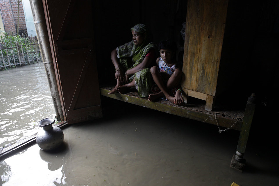 Photo -   A woman and a child sit on a bed after flood waters entered their house at Dhuhibali, about 70 kilometers (44 miles) west of Gauhati, India, Sunday, July 1, 2012. More than a week of heavy rains in Assam state have caused the massive Brahmaputra River, one of Asia's largest to exceed danger levels. Smaller rivers have also overflowed their banks.(AP Photo/Anupam Nath)