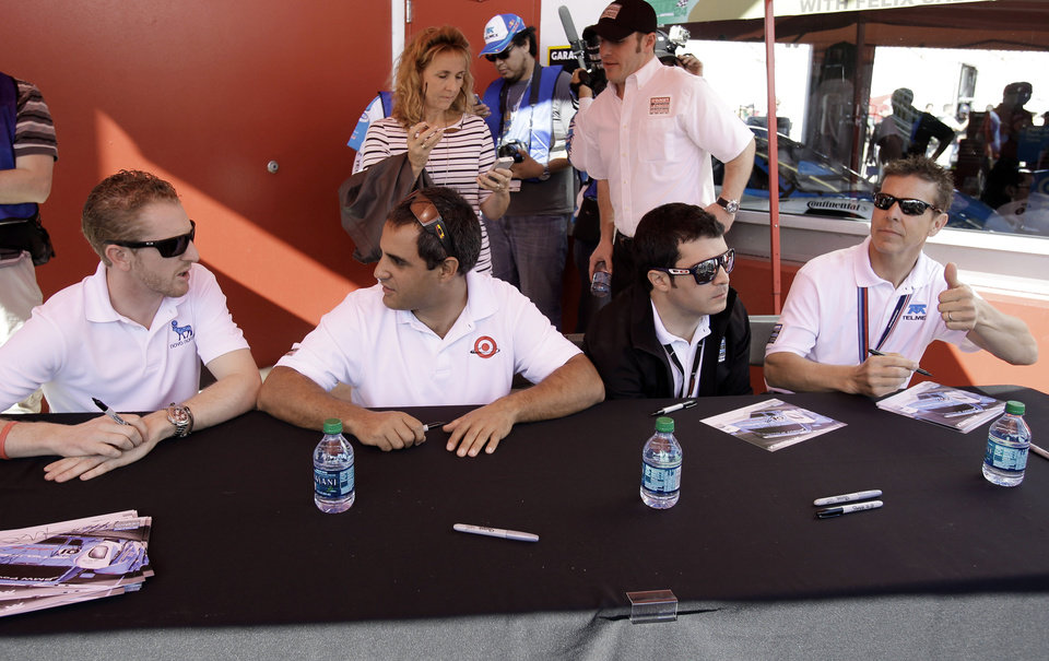 Photo - Drivers for the Ganassi Racing (01) BMW Riley, from left, Charlie Kimball, of England, Juan Pablo Montoya, of Colombia, Memo Rojas, of Mexico and Scott Pruett, sign autographs for fans prior to the Grand-Am Series Rolex 24 hour auto race at Daytona International Speedway, Saturday, Jan. 26, 2013, in Daytona Beach, Fla. (AP Photo/John Raoux)