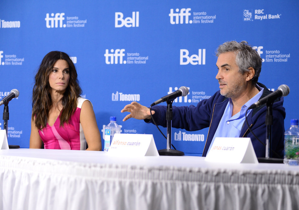 "Photo - Actress Sandra Bullock, left, and director Alfonso Cuaron participate in the press conference for ""Gravity"" on day 5 of the 2013 Toronto International Film Festival at the TIFF Bell Lightbox on Monday, Sept. 9, 2013 in Toronto. (Photo by Evan Agostini/Invision/AP) ORG XMIT: TOEA114"
