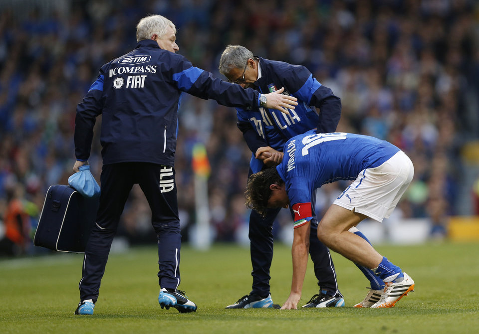 Photo - Italy's Riccardo Montolivo, lower right, limps off the pitch after getting injured from a tackle during their international friendly soccer match at Craven Cottage, London, Saturday, May 31, 2014. (AP Photo/Sang Tan)