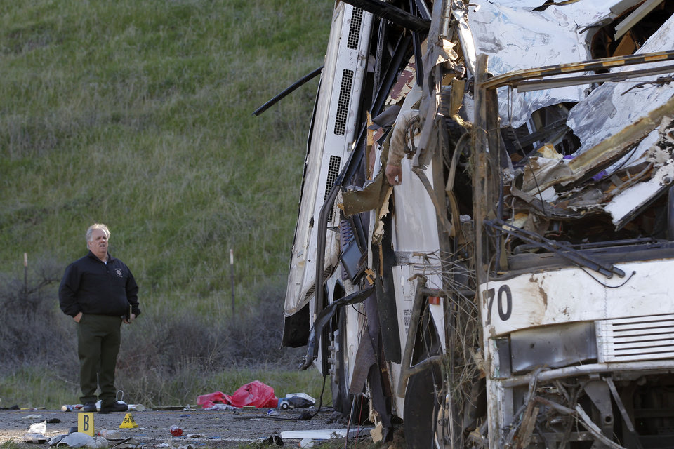 An official views the wreckage of a tour bus Monday Feb. 4, 2012 near San Bernardino, Calif.  The tour bus carrying dozens of men, women and children from Tijuana, Mexico, crashed in the mountains of Southern California  Sunday killing at least eight people, authorities said.  ( AP Photo/Nick Ut)