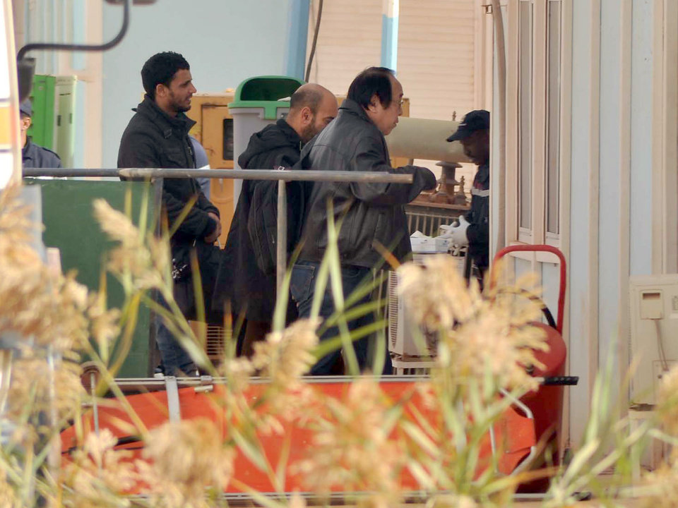An unidentified person right, is followed by Algerian officials as they enter a morgue in Ain Amenas Algeria Monday, Jan. 21, 2013,  where the bodies of the persons killed during the hostage situation at the gas plant in Ain Amenas,. At least 81 people have been reported dead, including 32 Islamist militants, after a bloody, four-day hostage situation at Algeria's remote Ain Amenas natural gas plant. (AP Photo/Anis Belghoul)