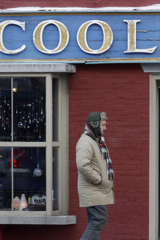 A man walks by a shop on Main St. in freezing temperatures on Wednesday, Jan. 23, 2013 in Montpelier, Vt. Sub-zero low temperatures are forecast for the area.  (AP Photo/Toby Talbot)