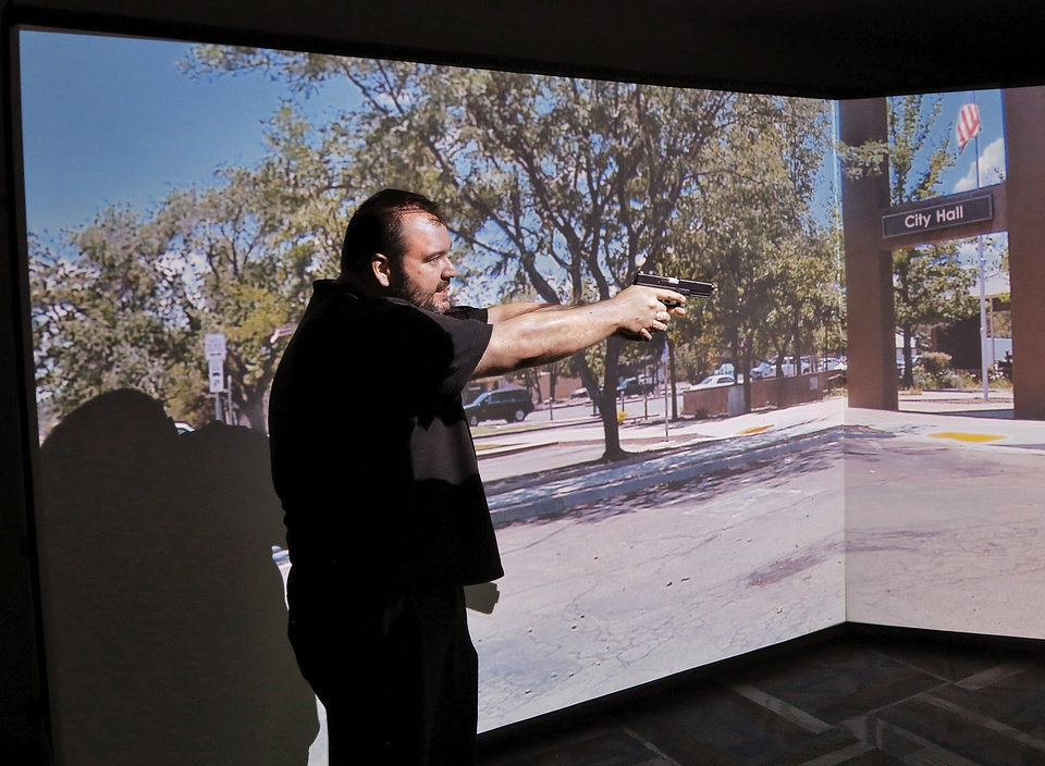 Photo -  Reporter Matt Dinger points his pistol and gives verbal commands while participating in a training scenario on Midwest City police's computerized shooting simulator. [Photo by Jim Beckel, The Oklahoman]