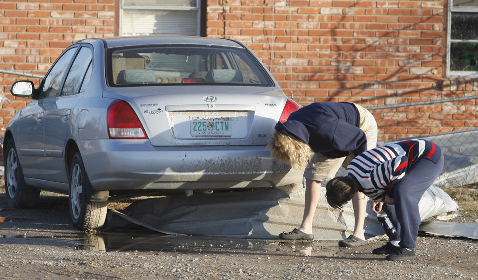 Photo - Lana Hartmon (left) and Carol McFarland try to figure a way to remove a piece of a metal roof from under McFarland's car as residents see the damage from Tuesday's deadly tornado in  Lone Grove, Okla., on Wednesday, Feb. 11, 2009.   Photo by Steve Sisney, The Oklahoman