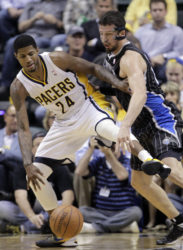 Photo -   Orlando Magic forward Hedo Turkoglu, right, defends Indiana Pacers guard Paul George in the first half of Game 5 of an NBA basketball first-round playoff series, in Indianapolis on Tuesday, May 8, 2012. (AP Photo/Michael Conroy)