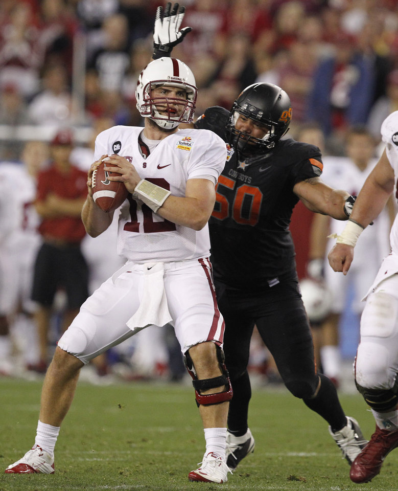 Photo - Stanford quarterback Andrew Luck (12)  looks downfield just before getting sacked by Oklahoma State defensive end Jamie Blatnick (50) during the second half of the Fiesta Bowl NCAA college football game Monday, Jan. 2, 2012, in Glendale, Ariz. (AP Photo/Ross D. Franklin)