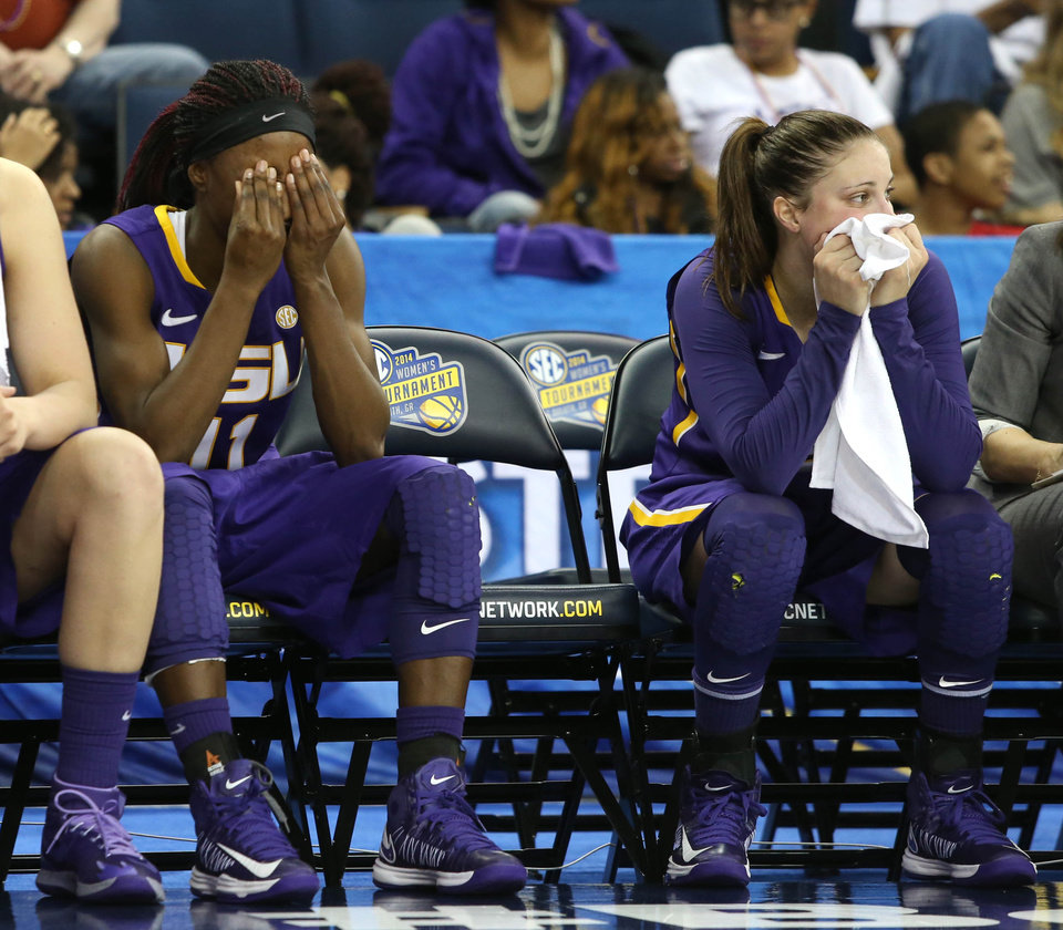 Photo - LSU guard Raigyne Moncrief, left, and guard Jeanne Kenney react on the bench in the closing minute of the team's to Tennessee in an NCAA college basketball game in the quarterfinals of the Southeastern Conference women's tournament, Friday, March 7, 2014, in Duluth, Ga. Tennessee defeated LSU 77-65. (AP Photo/Jason Getz)