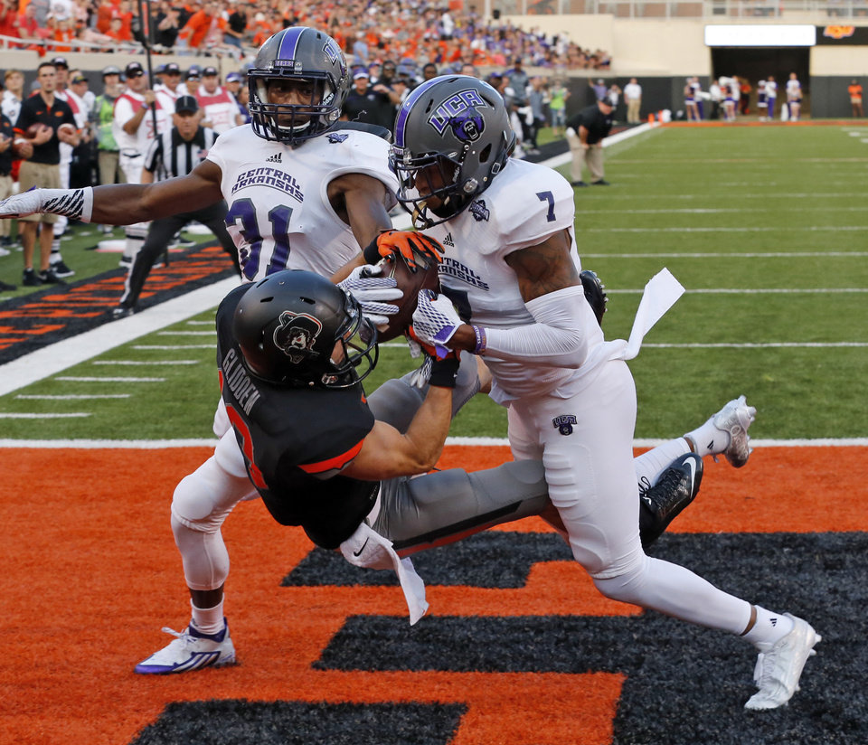 Photo - Oklahoma State's David Glidden (13) and Central Arkansas' Bobby Watkins (7) fight for a ball eventually ruled an incompletion during the college football game between the Oklahoma State Cowboys (OSU) and the Central Arkansas Bears at Boone Pickens Stadium in Stillwater, Okla., Saturday, Sept. 12, 2015. Photo by Steve Sisney, The Oklahoman