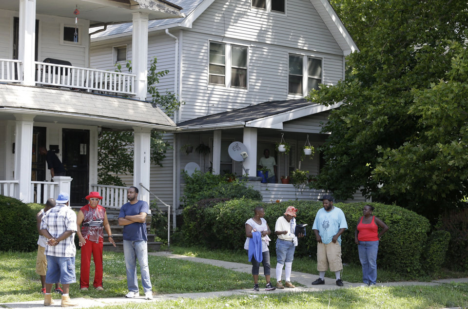 Photo - East Cleveland residents watch the scene  Sunday, July 21, 2013, close to where three bodies were recently found in East Cleveland, Ohio. The bodies, believed to be female, were found about 100 to 200 yards (90 to 180 meters) apart, and a 35-year-old man was arrested and is a suspect in all three deaths, though he has not yet been charged, East Cleveland Mayor Gary Norton said Saturday.(AP Photo/Tony Dejak)