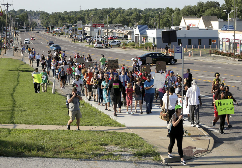 Photo - Protesters march Tuesday, Aug. 19, 2014, for Michael Brown, who was killed by police Aug. 9 in Ferguson, Mo. Ferguson's leaders urged residents Tuesday to stay home after dark to