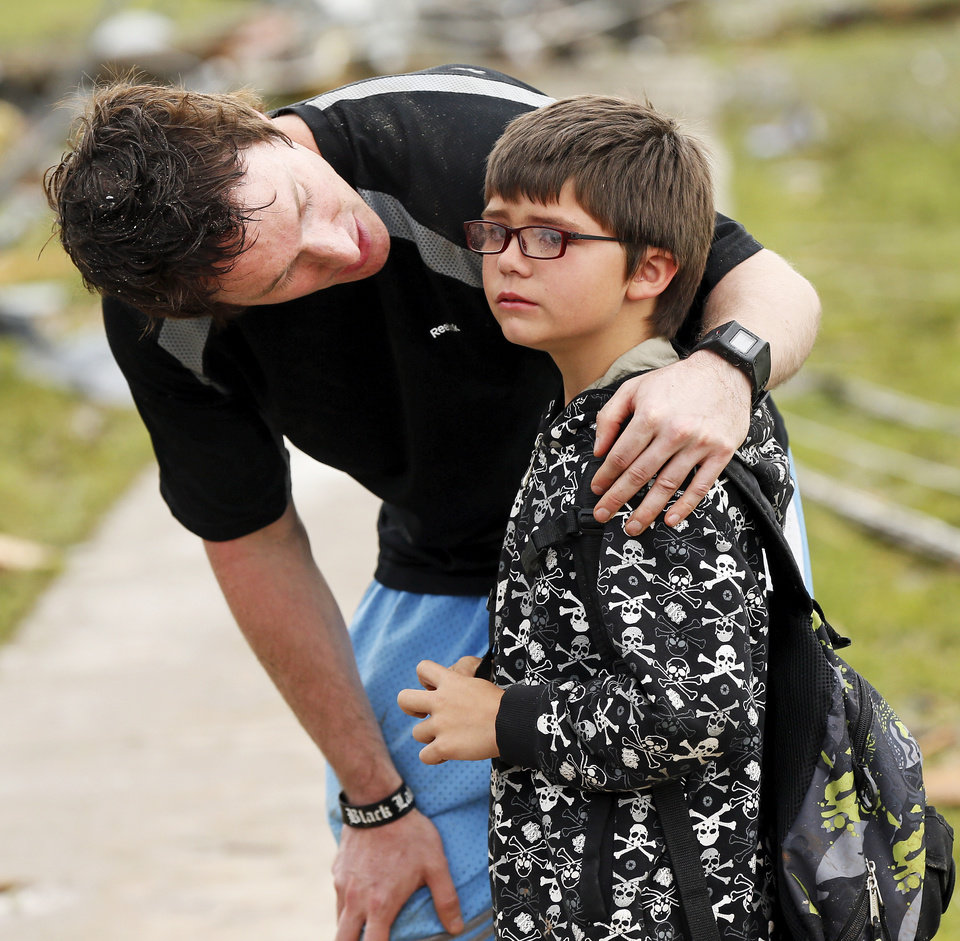 Briarwood Elementary P.E. teacher Mike Murphy comforts Aiden Stuck, 7, as he waits for his mother at the school after a tornado destroyed Briarwood Elementary and struck south Oklahoma City and Moore, Okla., Monday, May 20, 2013. Photo by Nate Billings, The Oklahoman