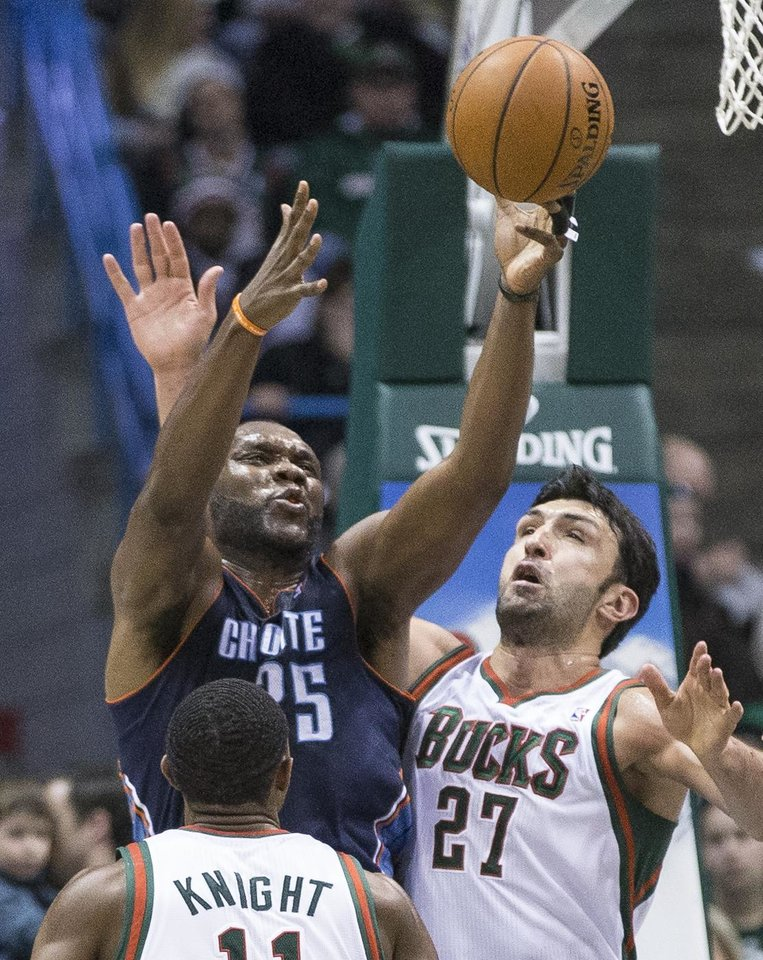 Photo - Milwaukee Bucks' Zaza Pachulia (27) and Brandon Knight defend against Charlotte Bobcats' Al Jefferson during the second half of an NBA basketball game on Sunday, March 16, 2014, in Milwaukee. (AP Photo/Tom Lynn)