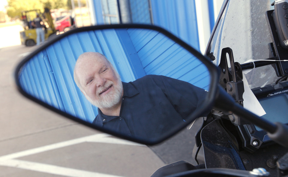 Photo -  Dan Maxey's reflection in the mirror of the Yamaha Super Tenere he rode to Alaska parked outside his shop in Oklahoma City on Tuesday. Photo by Paul B. Southerland, The Oklahoman   PAUL B. SOUTHERLAND -  PAUL B. SOUTHERLAND