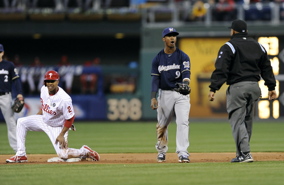Photo - Milwaukee Brewers shortstop Jean Segura (9) argues a call with umpire Adrian Johnson, right, as Philadelphia Phillies'  Ben Revere looks on from second base during the first inning of a baseball game on Wednesday, April 9, 2014, in Philadelphia. (AP Photo/Michael Perez)