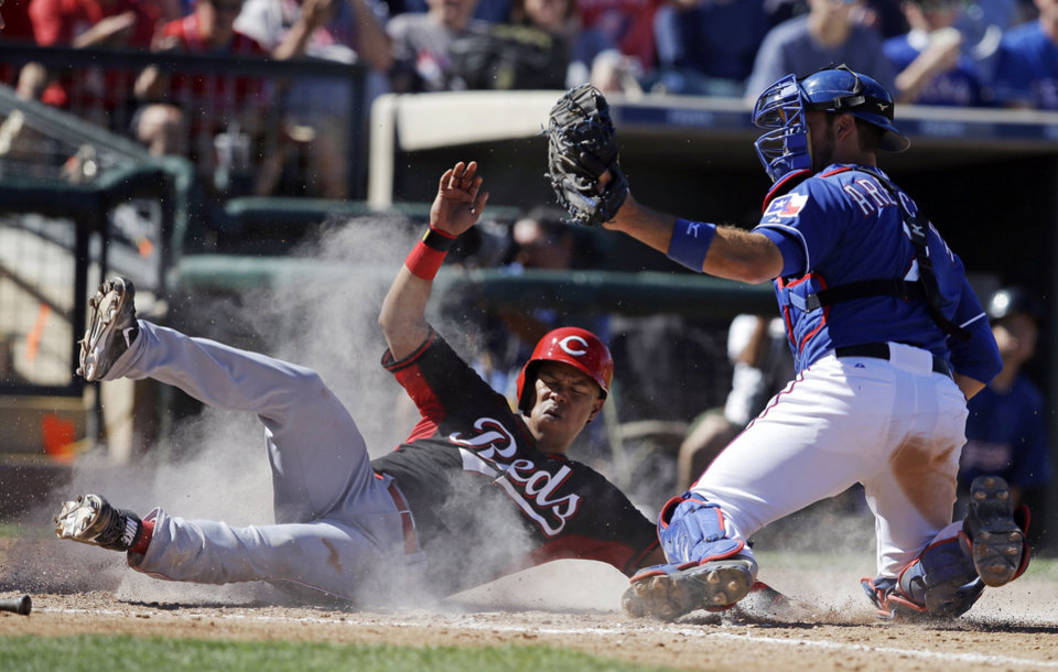Photo - Cincinnati Reds' Ramon Santiago, left, is tagged out by Texas Rangers' J.P. Arencibia during the fifth inning of a spring exhibition baseball game Monday, March 10, 2014, in Suprise, Ariz. (AP Photo/Darron Cummings)