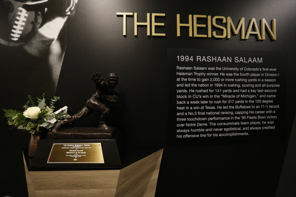 Photo - Inside the Champions Center at the University of Colorado, the 1994 Heisman Trophy for former Colorado running back Rashaan Salaam is adorned with a memorial flower Tuesday, Dec. 6, 2016, after Salaam's body was found Monday evening at a park, in Boulder, Colo. The Boulder County coroner's office said that it was still investigating the cause of the death of the 42-year-old Salaam. Police say foul play was not suspected. (AP Photo/Brennan Linsley)