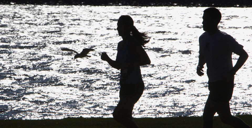 Photo - Runners pass Lake Hefner and a seagull in Stars and Stripes Park during the Tenth Annual Oklahoma City Memorial Marathon, Sunday, April 25, 2010.   Photo by David McDaniel, The Oklahoman ORG XMIT: KOD