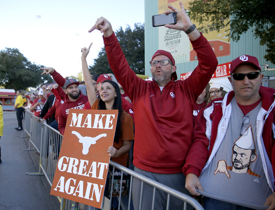 Photo - A Texas fan cheers as Oklahoma fans do the Horns Down as Texas arrives before the Red River Showdown college football game between the University of Oklahoma Sooners (OU) and the Texas Longhorns (UT) at Cotton Bowl Stadium in Dallas, Saturday, Oct. 12, 2019. [Sarah Phipps/The Oklahoman]