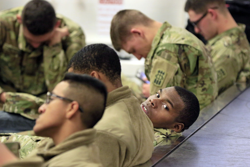 Photo - Andrew Jackson, from Tampa, FL, tries to rest against the baggage carousel while waiting for his flight, as soldiers from Ft. Sill gather at Will Rogers World Airport in Oklahoma City, Okla. on their way home for Christmas, Monday, Dec. 19, 2016.  Photo by Paul Hellstern, The Oklahoman