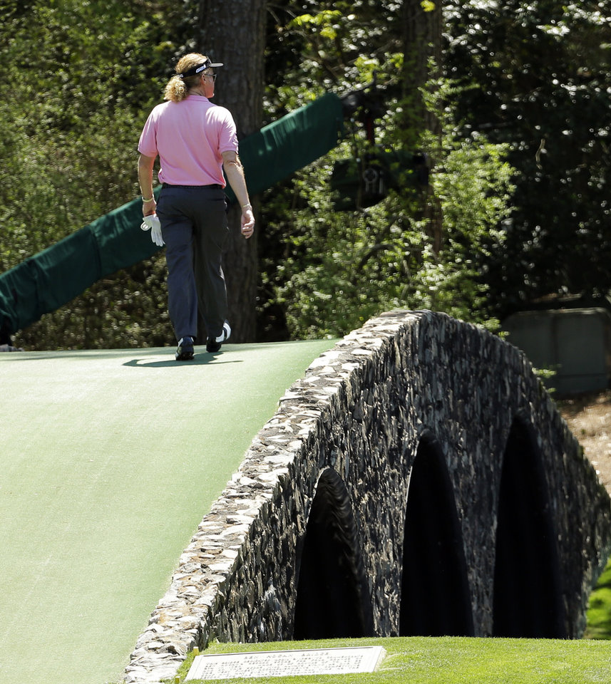 Photo - Miguel Angel Jimenez, of Spain, walks across the Hogan Bridge on the 12th fairway during the first round of the Masters golf tournament Thursday, April 10, 2014, in Augusta, Ga. (AP Photo/David J. Phillip)