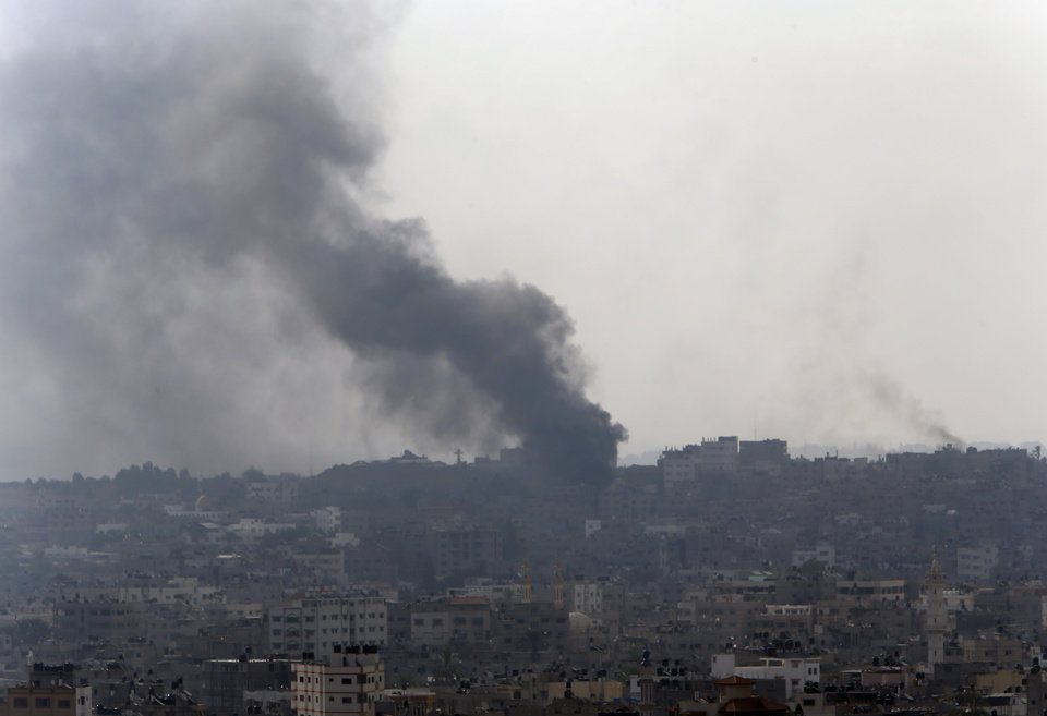 Photo - Smoke from Israeli strikes rises over Gaza City , northern Gaza Strip, Monday, July 21, 2014. The first major ground battle in two weeks of Israel-Hamas fighting exacted a steep price Sunday: It killed 65 Palestinians and 13 Israeli soldiers and forced thousands of terrified Palestinian civilians to flee Gaza City's Shijaiyah neighborhood, reportedly used to launch rockets at Israel and now devastated by the fighting. (AP Photo/Lefteris Pitarakis)