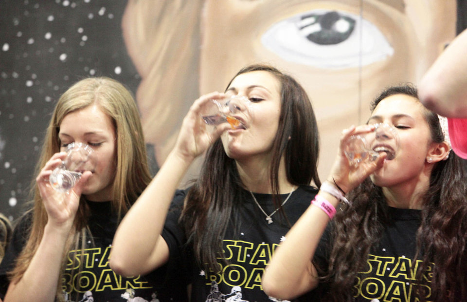 Photo - Sophomores Lauren Pitts, Abby Barnes and Jaclyn Hummel swallowed goldfish to raise money Swine Week. Photo By David McDaniel, The Oklahoman